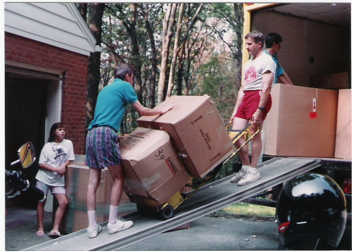 Board member Anthony Mediate moving boxes of supplies onto a truck, 1990.